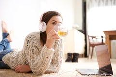 Tè bevente della giovane donna ed ascoltare la musica con le cuffie Fotografie Stock Libere da Diritti