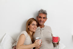 Tè bevente delle coppie felici nel letto Fotografia Stock