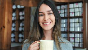 Tè bevente o caffè della bella ragazza in caffè Bellezza Woman di modello con la tazza della bevanda calda video d archivio