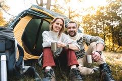 Tè bevente positivo della donna e dell'uomo vicino alla tenda Immagine Stock