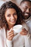 Tè bevente sorridente delle coppie afroamericane nel caffè immagini stock