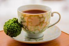 Tè caldo con il bergamotto sulla tavola di legno nel freddo fotografia stock libera da diritti