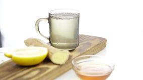 Tè che è versato nella tazza di tè trasparente di vetro con il limone e lo zenzero Bevanda di riscaldamento in freddo video d archivio