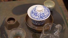 Tè che fa nella ciotola e negli oggetti ceramici per cerimonia di tè cinese video d archivio