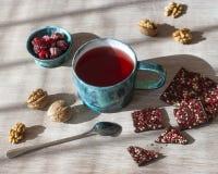 Tè, cioccolato, dadi e lamponi del lampone su una tavola di legno, fuoco selettivo fotografia stock libera da diritti