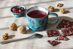 Tè, cioccolato, dadi e lamponi del lampone su una tavola di legno, fuoco selettivo immagine stock libera da diritti