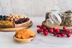 Tè con i frutti secchi e nocciole in ciotole di legno con la decorazione degli elementi fotografie stock