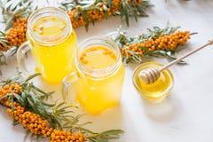 Tè con l'olivello spinoso ed il miele su un fondo leggero Fotografia Stock Libera da Diritti
