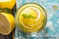 Tè con la menta e l'intero limone in una tazza trasparente Immagini Stock Libere da Diritti