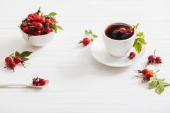 Tè con le bacche di una rosa canina su fondo di legno Fotografie Stock