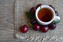Tè con le ciliege di recente selezionate in una tazza bianca su un panno della tela da imballaggio Tè di ghiaccio della ciliegia  Fotografia Stock