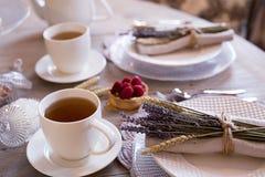 Tè con le tazze ed i dolci bianchi Immagini Stock