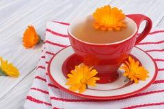 Tè del fiore della calendula sulla tovaglia a strisce Immagine Stock Libera da Diritti