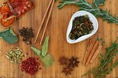 Tè della miscela asciutta di Oolong di cinese in una ciotola bianca Su un bordo di legno sparso molti ingredienti per tè Fotografia Stock