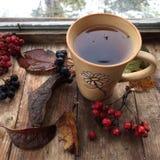 Tè di autunno: tazza bianca con tè nero su un fondo di legno Immagine Stock Libera da Diritti
