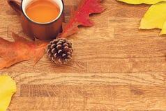 Tè di autunno in tazza d'annata marrone sulla vecchia tavola di legno rustica con le foglie e la conca di autunno fotografie stock