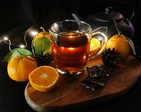 Tè di autunno in una tazza trasparente Mandarini tagliati su un fondo nero Cioccolato rotto garland Priorità bassa nera immagine stock libera da diritti