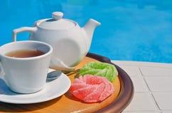 Tè di camomilla in una tazza davanti allo stagno fotografia stock