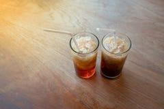 Tè di ghiaccio e caffè di ghiaccio tailandesi con paglia bianca in vetro trasparente su w fotografia stock
