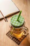 Tè di ghiaccio e libro in bianco sulla tavola Fotografie Stock