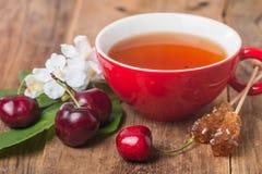 Tè di inglese nero in tazza rossa con la ciliegia Immagine Stock
