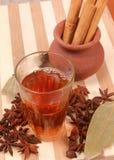 Tè di Masala in un vetro, con i bastoni di cannella & del caramon su un vaso Immagini Stock Libere da Diritti