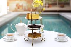 Tè di pomeriggio con la tazza di tè e la teiera sulla tavola con il dolce fotografia stock