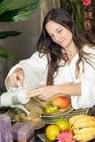 Tè di versamento della donna alla prima colazione - verticale Immagine Stock