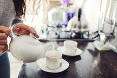 Tè di versamento della donna nella tazza ceramica alla tavola immagine stock