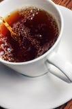 Tè di versamento in una tazza bianca Fotografia Stock