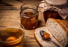 Tè e pane con la marmellata di arance su fondo di legno Fotografia Stock