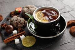Tè fragrante in una tazza nera su una banda nera con i biscotti, il limone, la cannella ed i frutti immagine stock libera da diritti