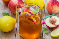 Tè ghiacciato con il limone e la pesca in un barattolo di muratore Bibita analcolica di estate Immagini Stock