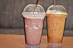 Tè ghiacciato del latte lattico e cacao ghiacciato in di vetro di plastica messo sull'i tum di legno Immagini Stock Libere da Diritti