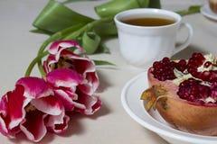 Tè, melograno e tulipani di mattina per la donna Immagini Stock