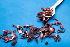 Tè naturale dell'ibisco in un cucchiaio e sparso su una tavola blu fotografie stock