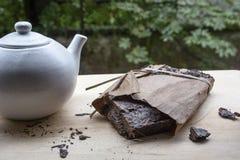 Tè naturale nero con la teiera bianca sulla tavola di legno Immagine Stock Libera da Diritti