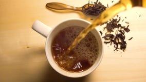 Tè nero caldo che versa in tazza bianca archivi video