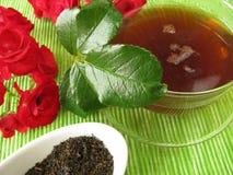 Tè nero con i fiori di rosa Fotografia Stock