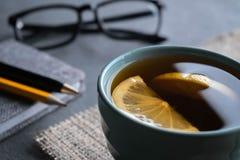 Tè nero con le fette del limone su un tovagliolo di tela da imballaggio con la penna del blocco note, una matita ed i vetri immagini stock