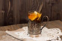 Tè nero nel supporto di tazza con il limone Fotografie Stock Libere da Diritti