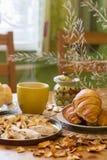 Tè nero in tazza gialla con i croissant, i panini ed i biscotti casalinghi immagini stock
