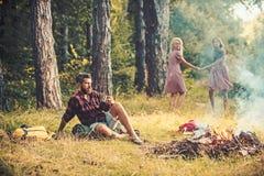 Tè o caffè barbuto della bevanda dell'uomo al falò con le donne su fondo vago L'uomo barbuto si siede a fuoco di accampamento fotografia stock libera da diritti