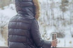 Tè o caffè caldo dal termos in mani della donna sul fondo della foresta di inverno ragazza che per mezzo di un termos dentro su u fotografie stock libere da diritti