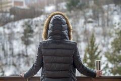 Tè o caffè caldo dal termos in mani della donna sul fondo della foresta di inverno ragazza che per mezzo di un termos dentro su u immagini stock libere da diritti