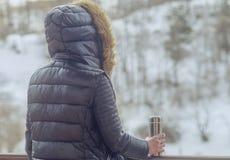 Tè o caffè caldo dal termos in mani della donna sul fondo della foresta di inverno ragazza che per mezzo di un termos dentro su u fotografia stock