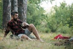 Tè o caffè della bevanda dei pantaloni a vita bassa al falò L'uomo barbuto si rilassa con la tazza a fuoco di accampamento Il tip fotografia stock libera da diritti