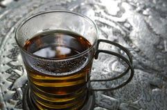 Tè orientale dentro un vetro con di piastra metallica fotografie stock