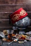 Tè turco con le tazze di vetro autentiche Due tazze di tè turco e dolci su fondo di legno scuro Immagini Stock Libere da Diritti