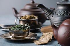 Tè verde asciutto in ciotola, fette croccanti del pane e teiere dell'argilla Fotografie Stock